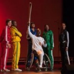 Adventist Church member Tyler Saunders, an alternate on the British basketball team for the 2012 Paralympics, holds a torch while surrounded by the cast of Beyond Gold, a theater production sponsored by the Adventist Church in London during the Summer Gam. Image by Ansel Oliver/ANN