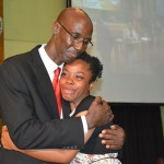 A teary-eye Aneak Riley from St. Mary hugs Pastor Everett Brown, president of the church in Jamaica, after the announcement that she is the Jamaica Union's 125th anniversary recipient of a full four-year scholarship at Northern Caribbean University, during the ceremony of Oct. 3, 2015. Image by