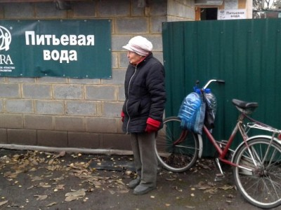 An elderly woman bringing empty water bottles for a refill at an ADRA water-filter station in eastern Ukraine. Images by ADRA