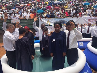 """Pastors pray for four new believers before baptizing them. More than 4,000 new members were baptized at Estadio Universitario de Caracas, during the church's """"Lord Transform Me,"""" evangelism program on Apr. 16, 2016. Image by Libna Stevens/IAD"""
