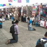 Adventist youth kneel along a large market place in the city of Oaxaca, in the state of Oaxaca, Mexico, during a youth evangelism initiative in July, 2016. Some 136 young people from across the church in Mexico's Inter-Oceanic region two part of a two-week evangelism and missionary impact initiative. Image by Inter-Oceanic Mexican Union.
