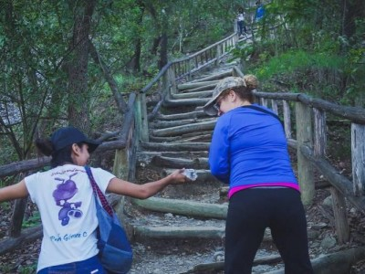 A young woman handing a bottle of water to a hiker in Monterrey, Mexico, on Friday. (Photos: Global PCM Weekend / Facebook)